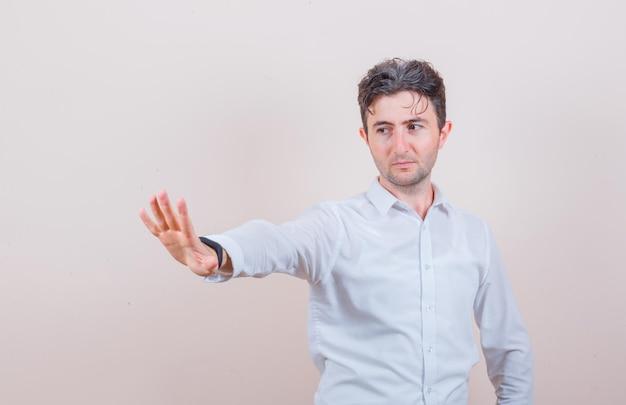 Junger mann im weißen hemd mit stopp-geste und fokussiertem blick