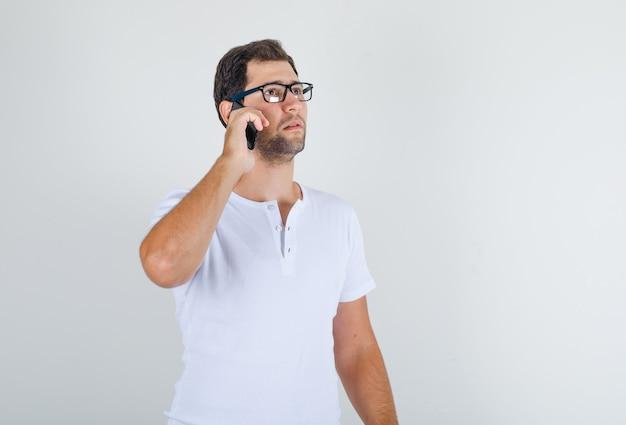 Junger mann im weißen t-shirt, brille, die auf handy spricht und nachdenklich aussieht