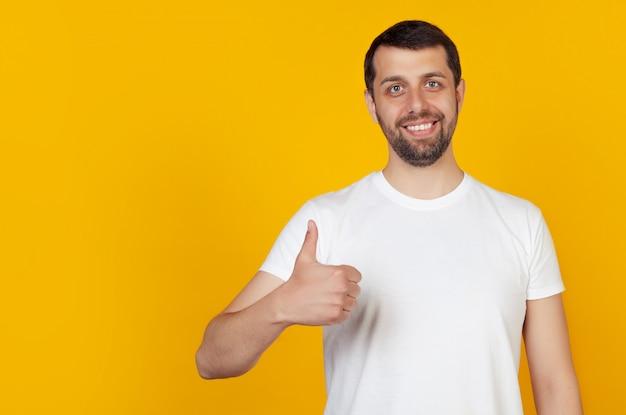 Junger mann im weißen t-shirt, das daumen oben mit einem glücklichen lächeln zeigt