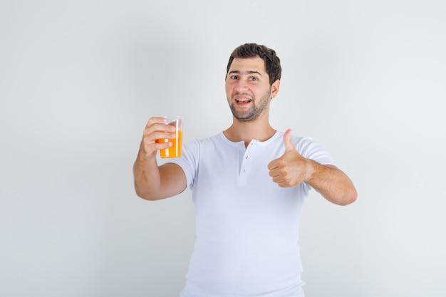 Junger mann im weißen t-shirt, das daumen oben mit glas saft zeigt und glücklich schaut