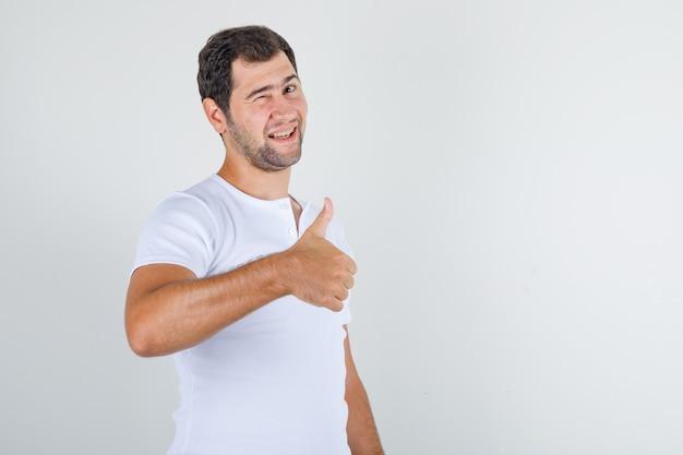 Junger mann im weißen t-shirt, das daumen oben und blinkendes auge zeigt