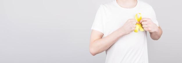 Junger mann im weißen t-shirt, das gelbes bandbewusstseinssymbol für selbstmord hält