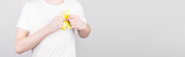 Junger mann im weißen t-shirt, das gelbes bandbewusstseinssymbol für selbstmord, sarkomknochenkrebs, blasenkrebs, leberkrebs und kinderkrebskonzept hält