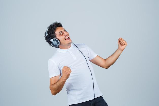 Junger mann im weißen t-shirt, das gewinnergeste zeigt und glückselig aussieht, vorderansicht.