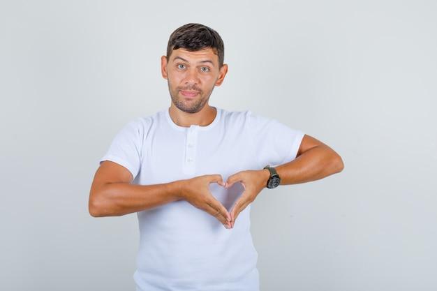Junger mann im weißen t-shirt, das herzgeste mit den fingern macht und positiv, vorderansicht schaut.