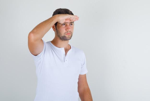Junger mann im weißen t-shirt, das mit hand auf stirn voraus schaut