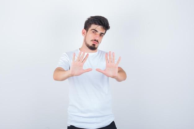 Junger mann im weißen t-shirt, das stoppgeste zeigt und selbstbewusst aussieht