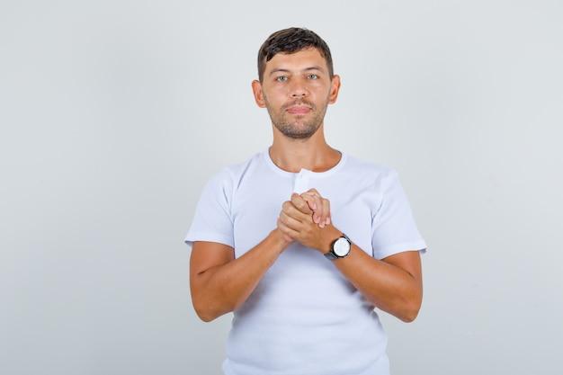 Junger mann im weißen t-shirt, das zusammengepresste hände fasst, vorderansicht.