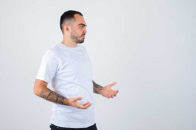 Junger mann im weißen t-shirt, der eine hand streckt, als er etwas hält und optimistisch aussieht