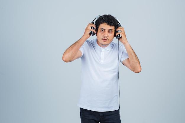 Junger mann im weißen t-shirt, der musik mit kopfhörern genießt und fokussiert, vorderansicht schaut.