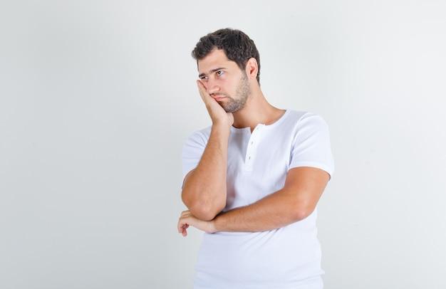 Junger mann im weißen t-shirt, der seine wange auf erhobene handfläche stützt und nachdenklich aussieht