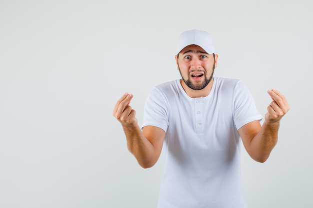 Junger mann im weißen t-shirt gestikuliert mit den fingern, um etwas zu erklären und besorgt auszusehen, vorderansicht.