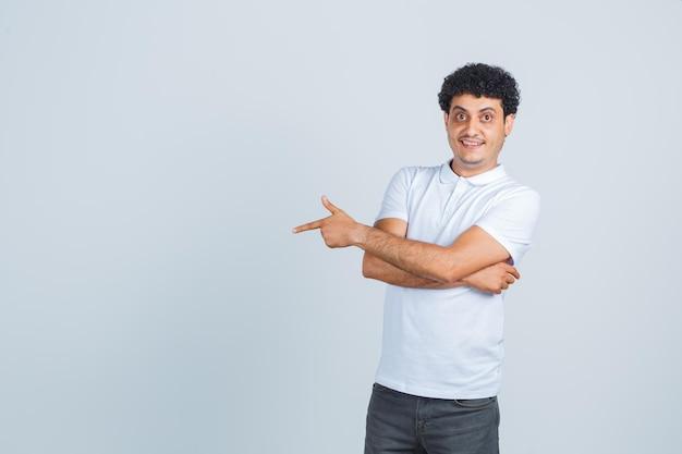 Junger mann im weißen t-shirt, hose zur seite zeigend und fröhlich aussehend, vorderansicht.