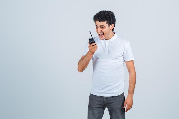 Junger mann im weißen t-shirt, hosen mit polizei-walkie-talkie-telefon und aufgeregt, vorderansicht.
