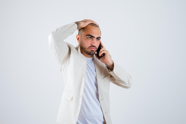 Junger mann im weißen t-shirt, jacke, die mit dem telefon spricht und die hand auf den kopf legt und wütend aussieht, vorderansicht.