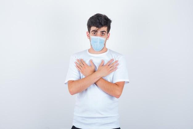 Junger mann im weißen t-shirt, maske mit gekreuzten händen auf der brust und selbstbewusst aussehend looking