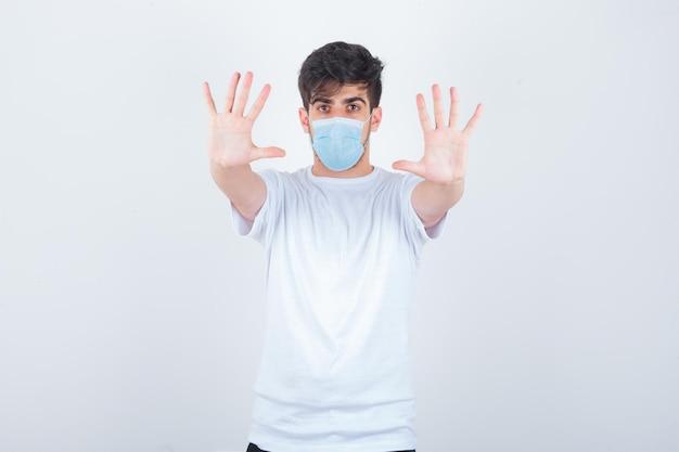 Junger mann im weißen t-shirt, maske mit stopp-geste und selbstbewusstem blick