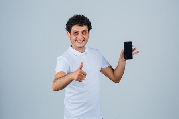 Junger mann im weißen t-shirt mit handy, daumen hoch und fröhlich aussehend, vorderansicht.