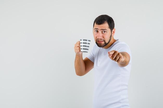 Junger mann im weißen t-shirt trinkend, während auf nach vorne zeigend und aufgeregt, vorderansicht schauend. platz für text