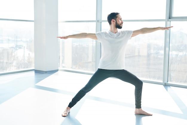 Junger mann in aktivkleidung, der mit ausgestreckten armen auf dem boden des fitnessraums steht und während der yogapraxis das gleichgewicht hält