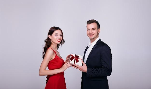 Junger mann in anzug und frau in einem roten kleid, die eine geschenkbox zusammen auf grauem hintergrund halten