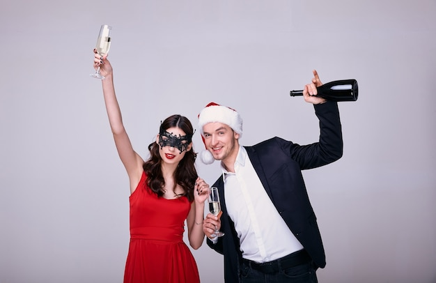 Junger mann in anzug und weihnachtsmütze und frau in rotem kleid und maske halten sektglas und flasche