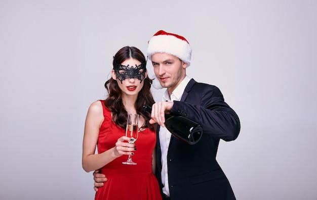Junger mann in anzug und weihnachtsmütze und frau in rotem kleid und maske mit champagnerglas