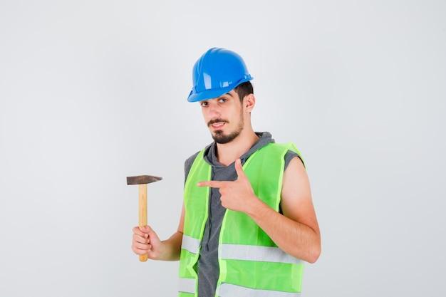 Junger mann in bauuniform, der mit dem zeigefinger auf die axt zeigt und glücklich aussieht