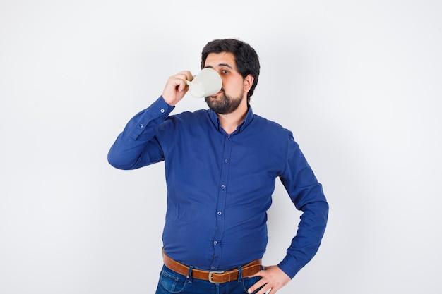 Junger mann in blauem hemd und jeans, der die hand an der taille hält, während er eine tasse wasser trinkt und optimistisch aussieht, vorderansicht.