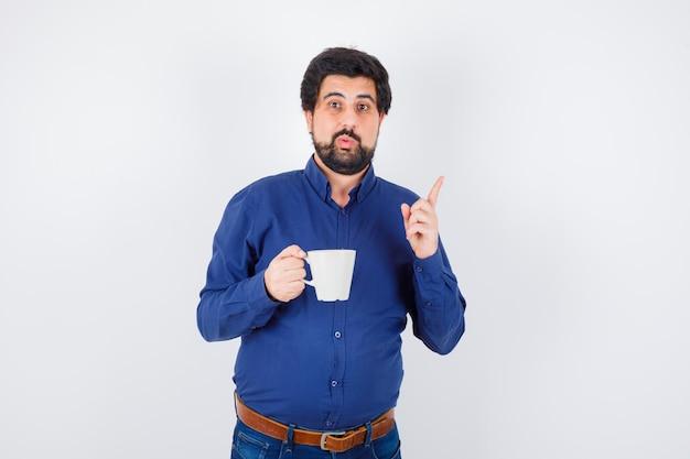 Junger mann in blauem hemd und jeans, der eine tasse hält und den zeigefinger in der heureka-geste hebt und optimistisch aussieht, vorderansicht.