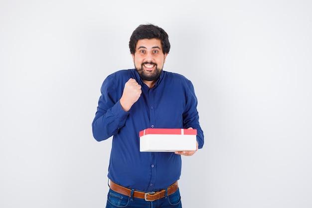 Junger mann in blauem hemd und jeans mit geschenkbox und geballter faust und glücklich aussehend, vorderansicht.