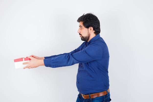 Junger mann in blauem hemd und jeans präsentiert geschenkbox und sieht ernst aus, vorderansicht.