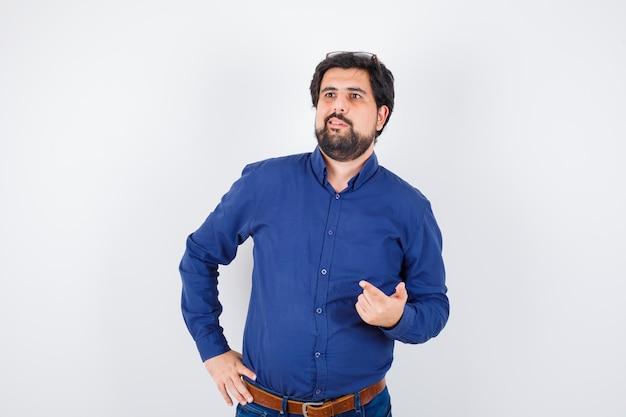 Junger mann in blauem hemd und jeans zeigt mit dem finger auf exemplar, vorderansicht.
