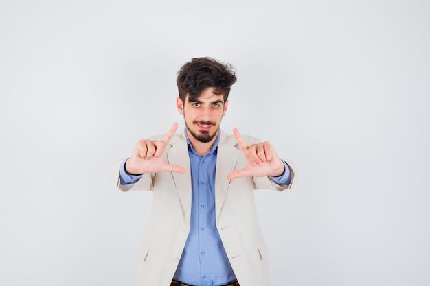Junger mann in blauem hemd und weißer anzugjacke, der so tut, als würde er ein foto machen und glücklich aussehen