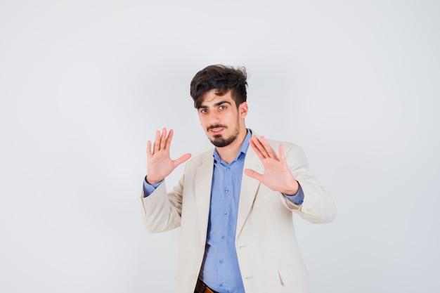 Junger mann in blauem hemd und weißer anzugjacke, der stoppschilder zeigt und glücklich aussieht