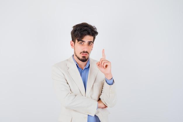 Junger mann in blauem t-shirt und weißer anzugjacke, der den zeigefinger in der heureka-geste hebt und ernst aussieht