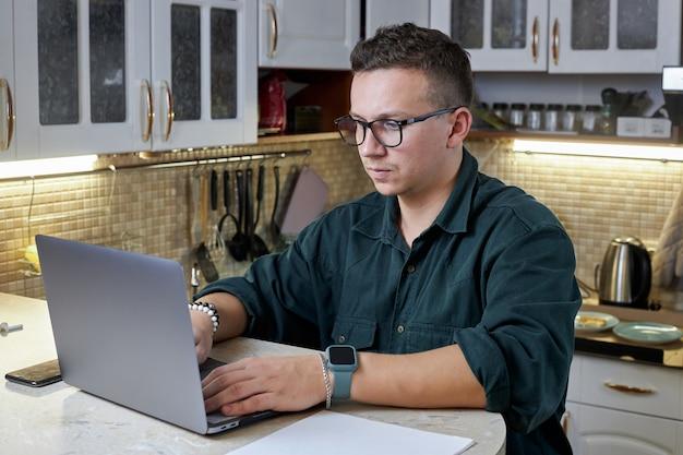 Junger mann in brille arbeitet an seinem laptop an selbstisolation zu hause. technologie-, remote-job- und lifestyle-konzept.