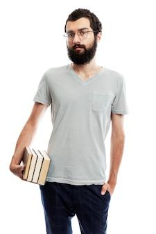 Junger mann in brille und mit bart mit büchern in der hand. schul-und berufsbildung.
