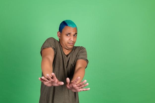 Junger mann in casual auf grüner wand bedeckt mit händen aus angst vor ekel
