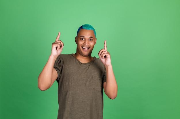 Junger mann in casual auf grüner wand blaues haar fröhlicher positiver zeigefinger nach oben