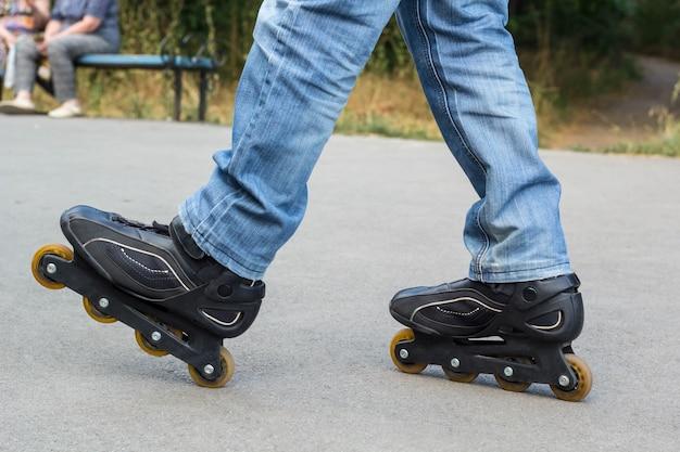 Junger mann in den blue jeans, die rollschuhe in der stadt reiten. beine hautnah