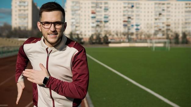 Junger mann in den gläsern, die auf einem stadion joggen