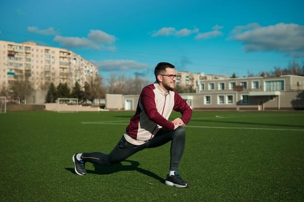 Junger mann in den gläsern, die auf einem stadion strecken
