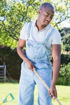 Junger mann in den jeansstoffen, die den garten harken