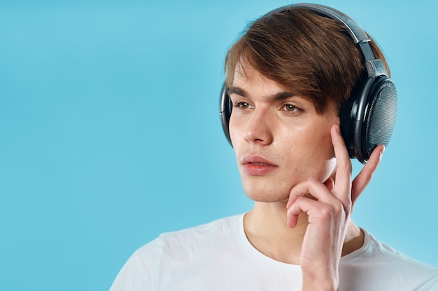Junger mann in den kopfhörern auf einem blauen hintergrund