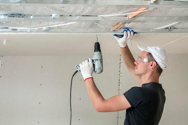 Junger mann in den schutzbrillen, die trockenmauer verschobene decke am metallrahmen reparieren