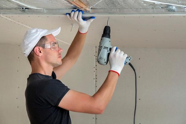 Junger mann in den schutzbrillen, die trockenmauer verschobene decke am metallrahmen unter verwendung des elektrischen schraubenziehers reparieren.