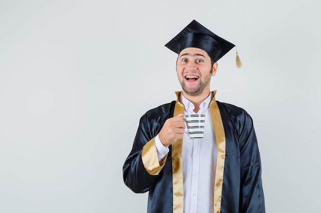 Junger mann in der abschlussuniform, die tasse kaffee hält und fröhlich, vorderansicht schaut.