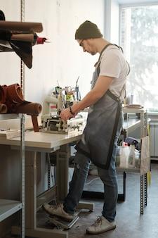 Junger mann in der arbeitskleidung, die vom tisch mit einem fuß auf dem pedal steht, während elektrische maschine zur herstellung von lederartikeln verwendet wird