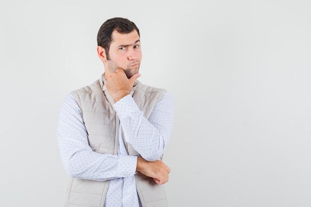 Junger mann in der beigen jacke, die in der denkenden haltung steht, während hand auf kinn setzt und nachdenklich, vorderansicht schaut.